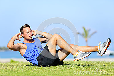 Sit ups - fitness man exercising sit up outside