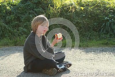 Sitting boy eating an apple