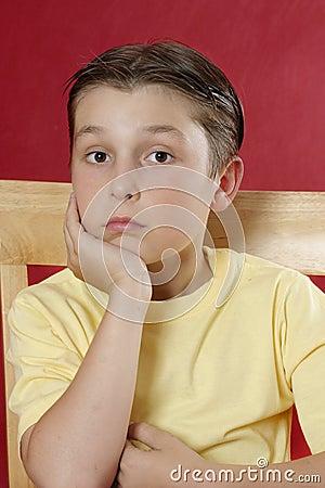 Sitting boy resting head on hand