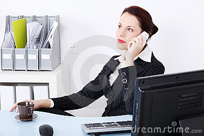 Sitting businesswoman answering the phone.