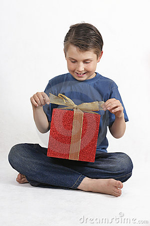 Sitting child opening a present