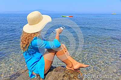 Sitting girl pointing remote control at sea