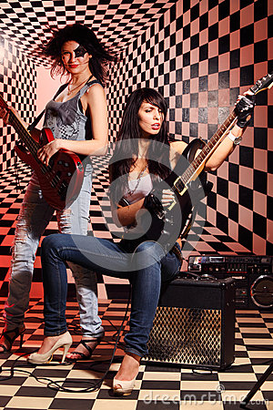 Sitting and standing women play electric guitar and sing