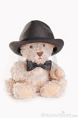 Sitting teddy bear with bow tie and hat