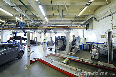Six black cars stand in garage with special equipment