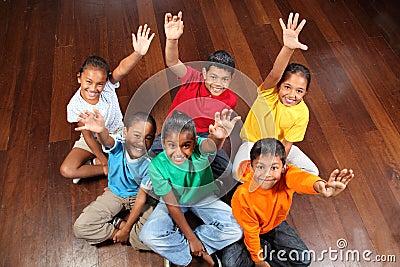 Six school children sitting in classroom hands up