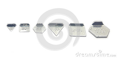Six small calibration weights on white background