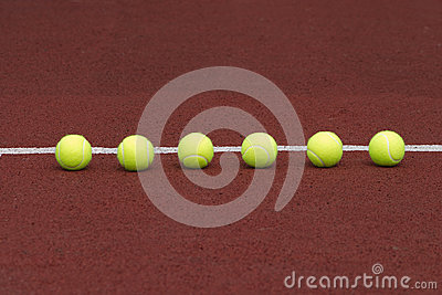 Six tennis balls in-line on court