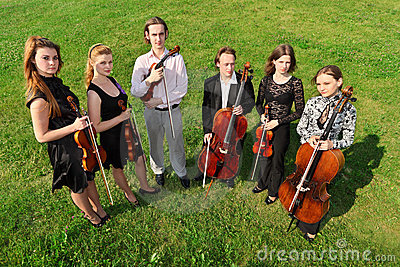 Six violinists stand semicircle on  grass