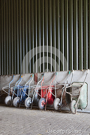 Free Six Wheelbarrows Rest Against Wall Of Farm Barn Stock Images - 54810464
