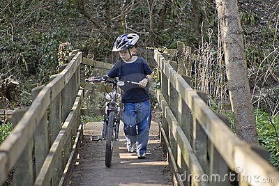 Six year old boy pushing a bike