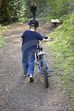 Six year old boy pushing a bike