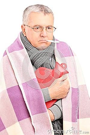 Sjuk pensionär med termometern i hans mun som är dold med filten