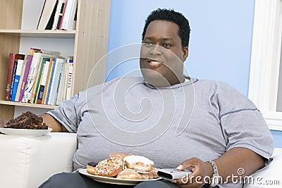 Sjukligt fett mansammanträde på soffan