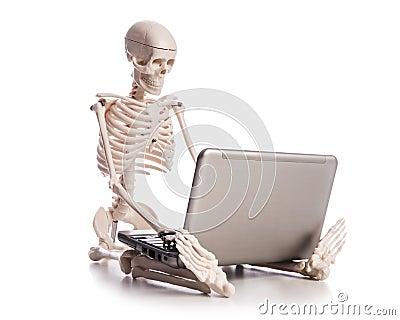 Skelett, das an Laptop arbeitet