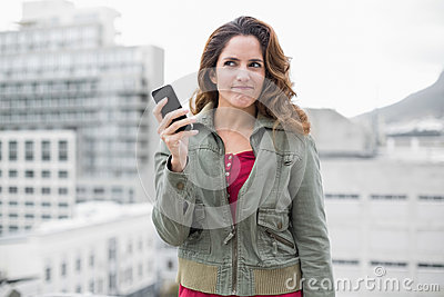 Skeptic gorgeous brunette in winter fashion holding smartphone