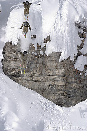Ski jump from a cliff in deep powder