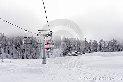 Ski lift with passengers in the chair Stock Photo
