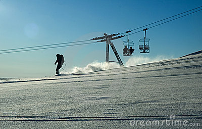 Ski lift and skiing in the powder snow