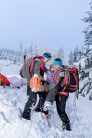 Ski patrol carry injured woman skier stretcher