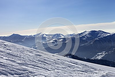 Ski slope with trace of ski, snowboards and mountains in haze
