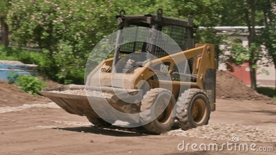 Skid steer loader moving sand soil at construction area outdoors stock video