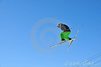 Skier in green jumping high