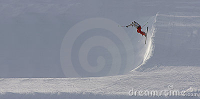 Skier jumping off steep slope