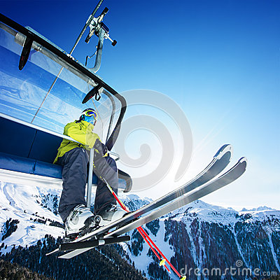 Skier siting on ski-lift - lift at sunny day and mountains