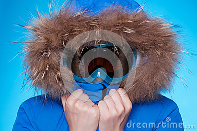 Skier in winter coat and mask feeling cold