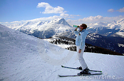 Skier woman drinking mineral water