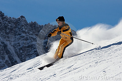 Skier woman in yellow suite moving down on slope