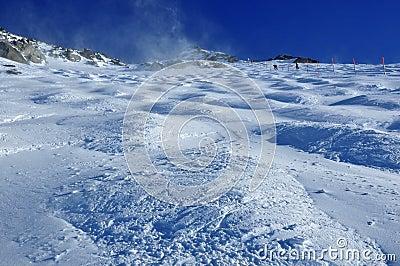 Skiers crossing onto a mogul field on a glacier