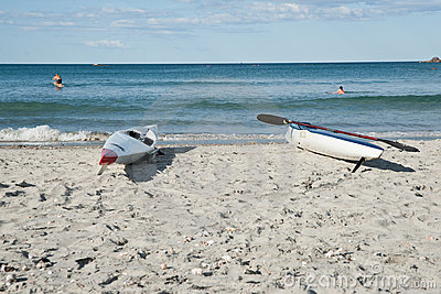 Skiffs on beach with surfers in background. Editorial Photography
