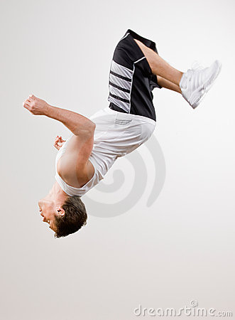 Skilled athlete doing somersault in mid-air