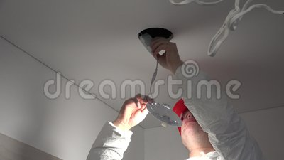 Skilled electrician man install modern led light into ceiling hole
