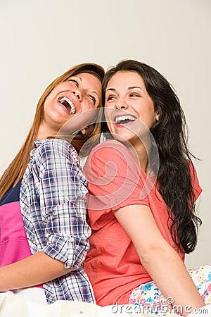 Skämtsamt sitta för vänner som är baksida mot baksida, och skratta