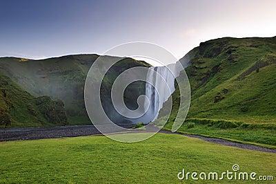 Skogafoss waterfall behing green cliffs, South Iceland