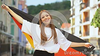 Skrovgig tonåring som viftar med tysk flagga och leker på kamera, nationell helgdag arkivfilmer
