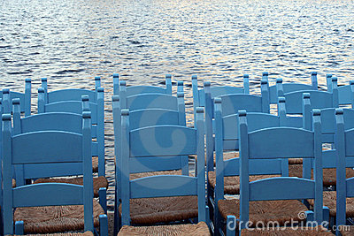 Sky blue chairs aligned on waterfront
