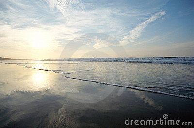 Sky, sun reflections on sandy beach and sea
