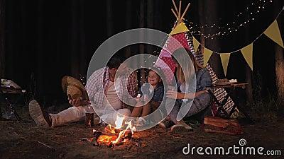 Släktingar på en trevlig liten flicka med föräldrar lyssnar glatt på roliga historier och dricker juice genom att tända eld på lager videofilmer