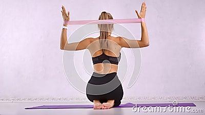 Slanke dametkoets maakt fysieke schokken voor de lucht voor achter het spierlichaam met behulp van rekuitrusting stock videobeelden
