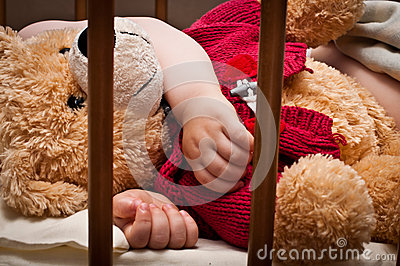 Sleeping baby with bear toy