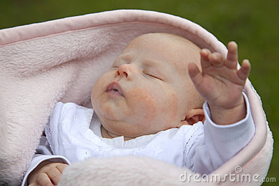 Sleeping baby girl reaching out hand