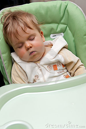 Sleeping baby in high chair