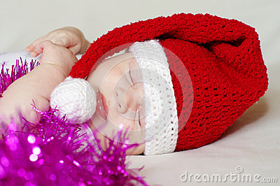 Sleeping baby in New Year s hat among spangle