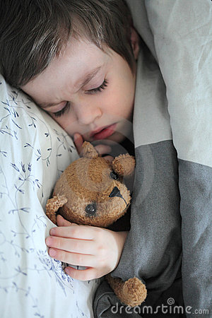 Sleeping boy with teddy bear toy