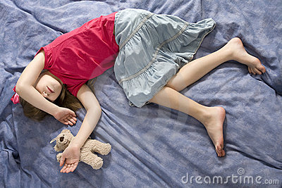 sleeping girl in bow with teddy-bear