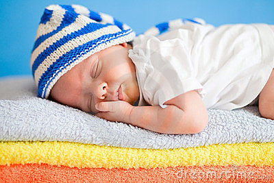 Sleeping newborn baby on colorful towels